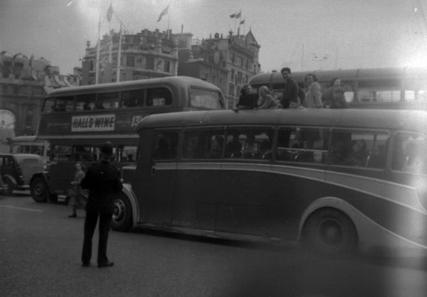 Policeman controlling traffic in Trafalgar Square - traffic turning into Whitehall. Photograph taken on the day of the 1953 Derby at Epsom. 6th June 1953