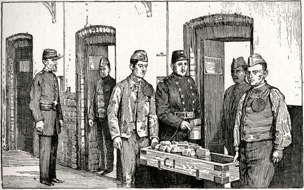 Uniformed warders supervise convicts delivering food cans and bread to the cells at an unnamed London prison
