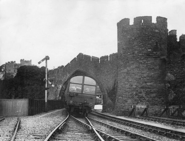 Back view of a train passing under an arch into Conway railway station, Conwy, North Wales