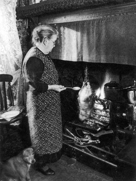 An old lady in overalls cooks her Christmas goose on an open fire. She uses an old method, whereby the goose is suspended by and revolves on twisted worsted. Somerset, England
