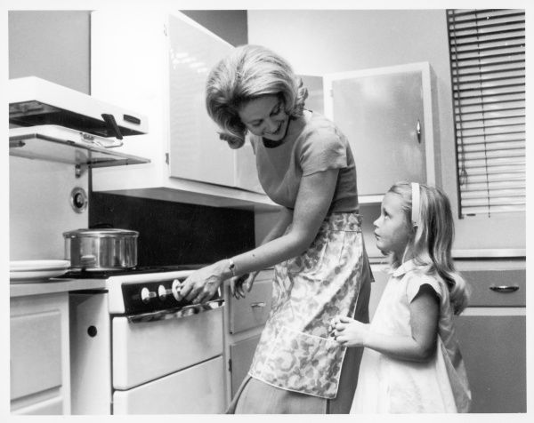 A little girl helps her mum prepare food in the kitchen