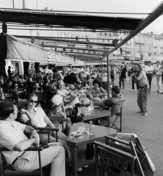 Cool customers at a street cafe in trendy St. Tropez, France, totally ignoring an uncool street ecapologist! Date: late 1960s