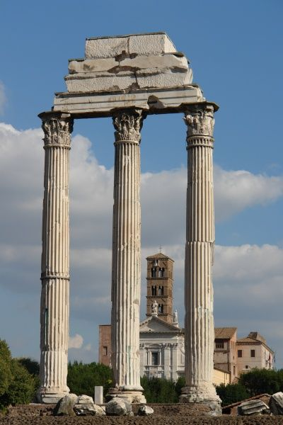 View of three Corinthian pillars in the Roman Forum, or Forum Romanum, with the Basilica di Massenzio (Basilica of Maxentius and Constantine) in the background