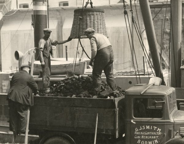 Cornish coalmen unloading coal from their lorry onto a ship before it sets sail from the harbour with its cargo of China clay