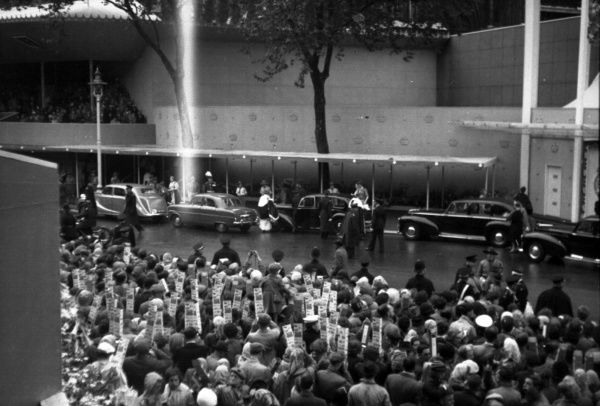 Cars arrive carrying foreign representtives; the crowd bring out their periscopes to see what they can of the acitivites on the other side of the road. Road litunersconsist of Police and St. John Ambulance Brigade. 1953