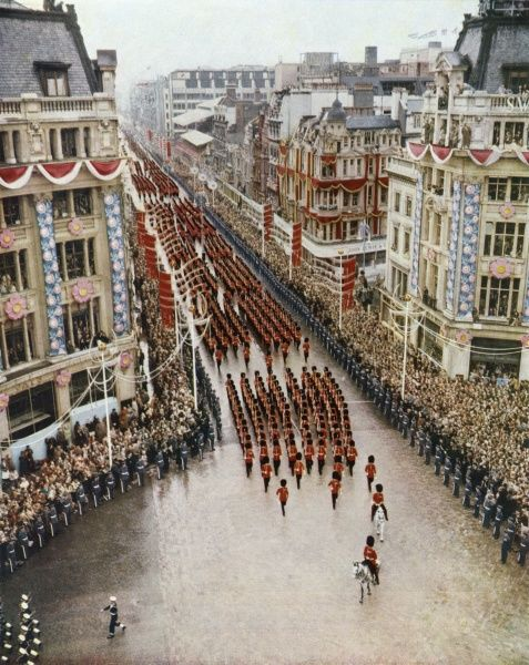 The colour and pageantry of the Coronation procession - detachments of the Foot Guards marching along Oxford Street into Oxford Circus showing the vast crowds lining the decorated route. Date: 1953