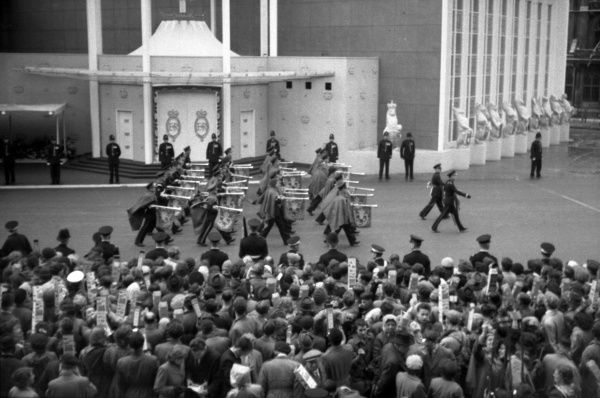Trumpeters march past the Abbey west door going to take up position on the Coronation route. Note: all wearing waterproof cloaks. 1953