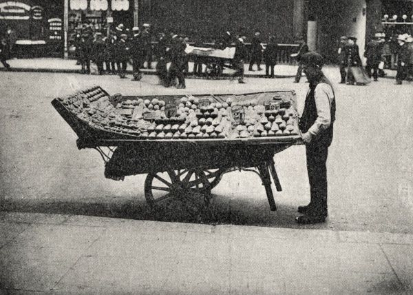 A coster with his barrow, loaded with fruit, on a London street