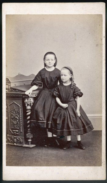Two girls in identical dresses with short full skirts, a row of pleated braid on the hem & sleeves & loose bodices with high round necks. Hair: hair net & chignon, ringlets