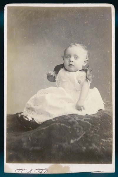 A baby sitting upright wears a broderie Anglaise frock with up-gathered sleeves & ribbon bows on the shoulders & leather shoes with a bar across the instep