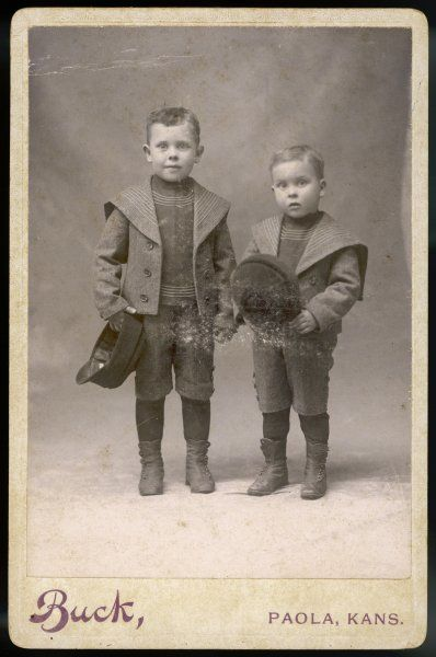 Two boys in knickerbocker suits with short S-B jackets with nautically inspired turnover collar & tunics trimmed with rows of narrow braid & peaked caps