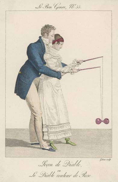 A man helps a lady to start off the diabolo on the string