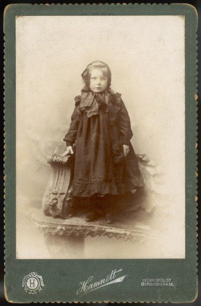A little girl wears a dark long sleeved yoked dress with tucks & a single flounce at the hem. She appears to have a large silk scarf tied round her neck