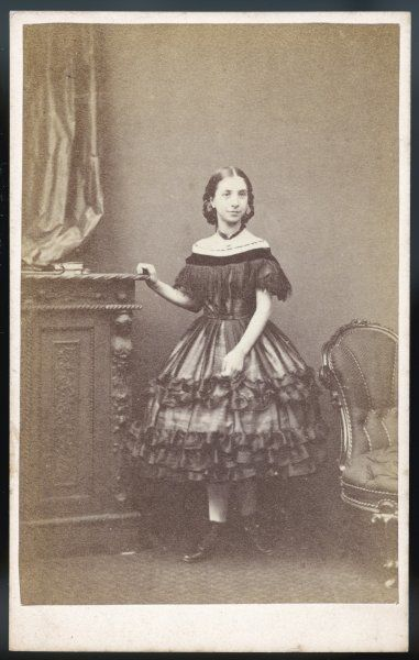 Girl: low bodice with deep bertha which hides the short sleeves, short skirt supported by a crinoline & trimmed with flounces, boots & stockings & a locket on a ribbon