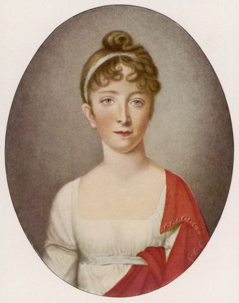 A young, blonde woman in a high-waisted, classical style, white muslin gown with low, square neckline. A red shawl is tucked into her belt. Her hair is dressed in a simple manner