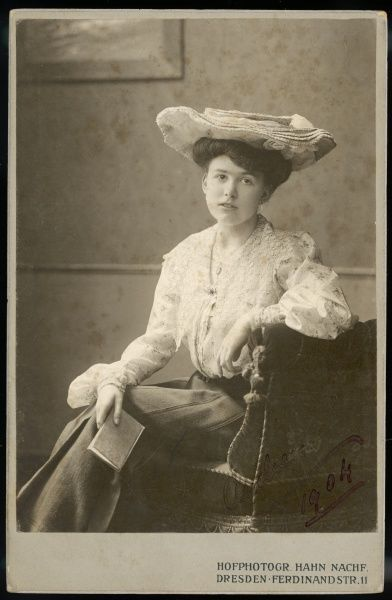 Audrey in 1904 wears a large flat straw hat, a box pleated skirt & a blouse with bishop sleeves in a pretty floral print. A lace fichu is pinned round her shoulders