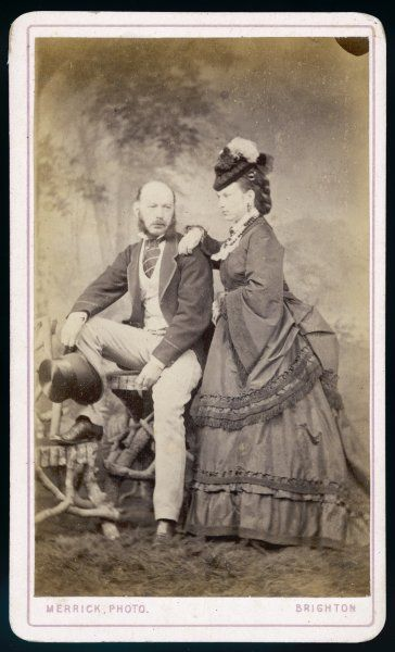 Woman: polonaise with pagoda sleeves, coils of false hair & a tiny hat tilted forwards. Man: light coloured trousers & waistcoat, striped cravat, short jacket with bound edges