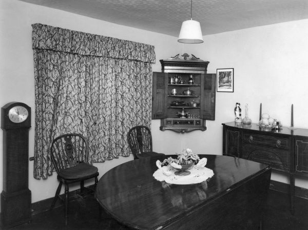 A lovely English country cottage dining room with traditional furniture. Date: 1930s