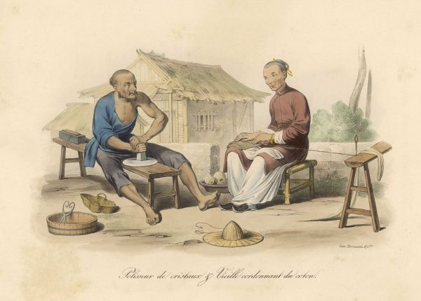 An old lady winds cotton into ballas, whilst a younger man polishes a crystal disk on a low bench. Their work in front of a modest homestead with a straw roof