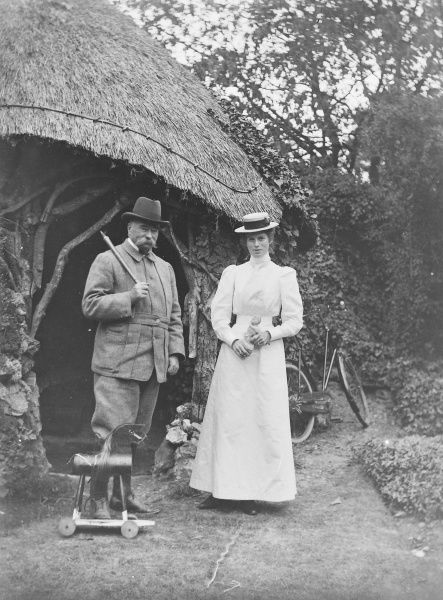 A moustachioed country gentleman and younger lady (his daughter?) in white dress and boater stand close to a thatch-roofed grotto and a child's hobby-horse