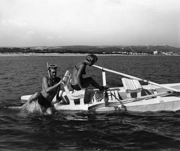 A young couple who have caught a fish appear to be in danger of capsizing as the man attempts to get back on board following some diving!  1960s