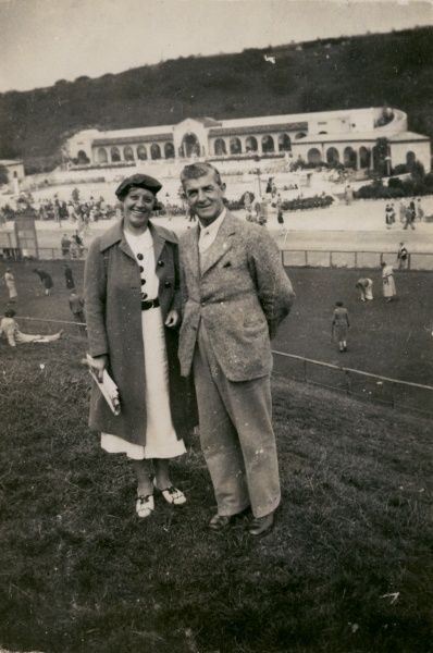 A couple on holiday in Scarborough, Yorkshire, with an outdoor swimming pool in the background. Date: circa 1940s