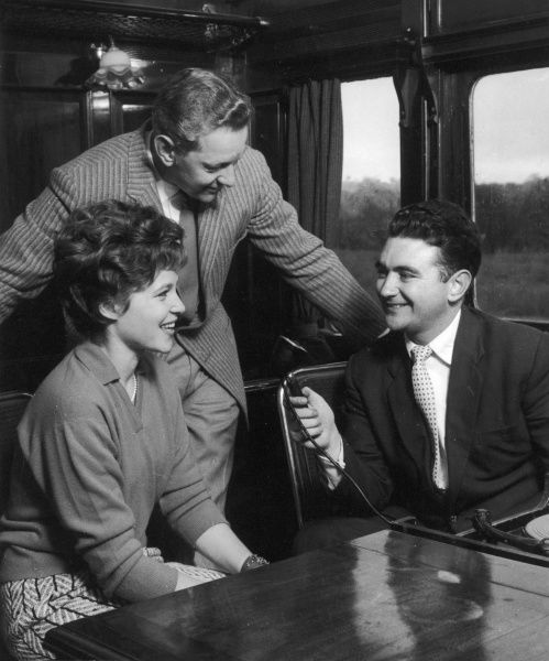 An interviewer holds up a microphone to ask a jolly middle aged couple a few questions on a train journey. Photograph by Heinz Zinram