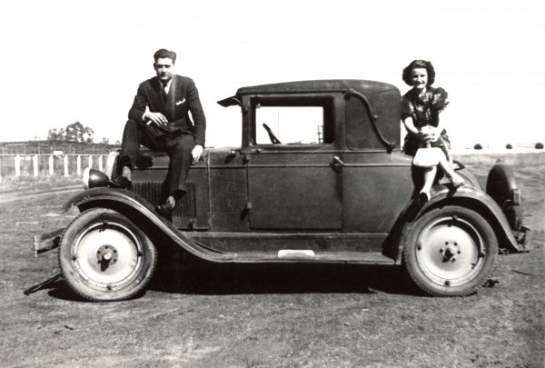 A couple posing on the bonnet and boot of a small coupe, parked in the middle of a field!