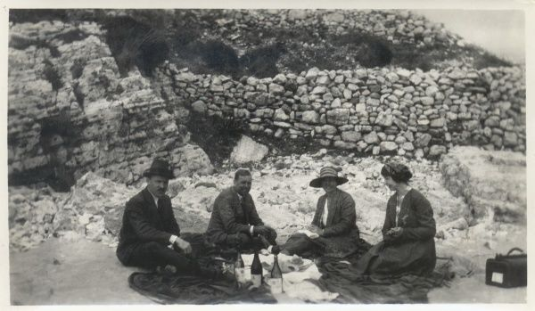 Two couples, one young, one middle aged,, enjoying a champagne picnic in front of a stone wall