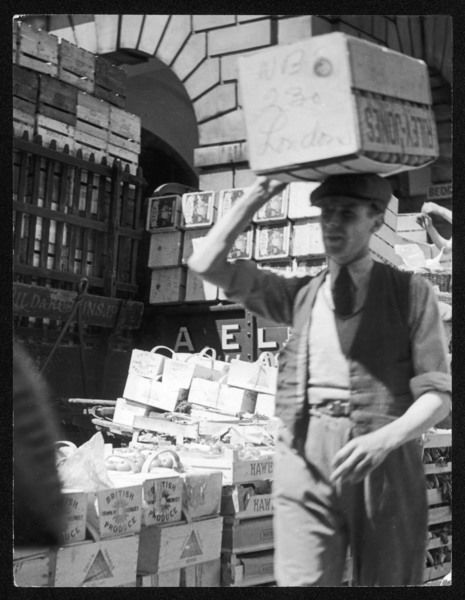 Fresh fruit arrives on a Spring morning at Covent Garden market. A man carries a crate of oranges on his head