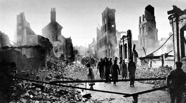 Photograph showing a scene of utter destruction in the centre of Coventry after the German air-raid of 14th November 1940. This image shows a group of civilians walking through the ruined streets of their city