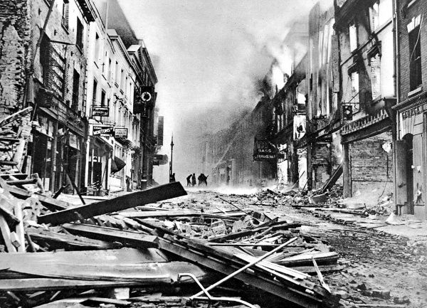 Photograph showing one of the main streets of Coventry, still burning after a German air-raid, 1940. In the background a group of fire-fighters pump water onto one of the blazes