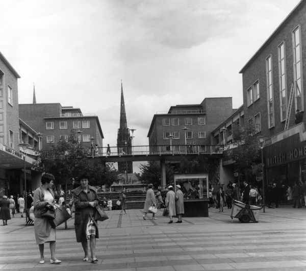 The rather stark modern shopping centre in Coventry with shoppers going about their business at British Home Stores or Marks and Spencer; Coventry Cathedral can be seen Date: 1960s