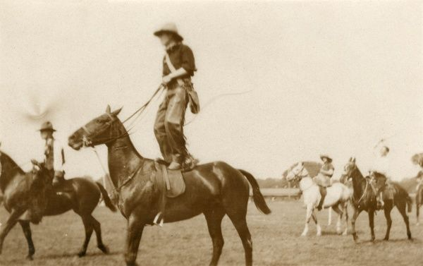 Cowboy riding on a horse, standing on its back