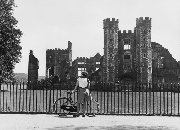 A female cyclist admires the ruins of Cowdray Castle, Sussex, England, Henry VIII awarded the house to Sir Anthony Brown, Master of the Horse, in 1542