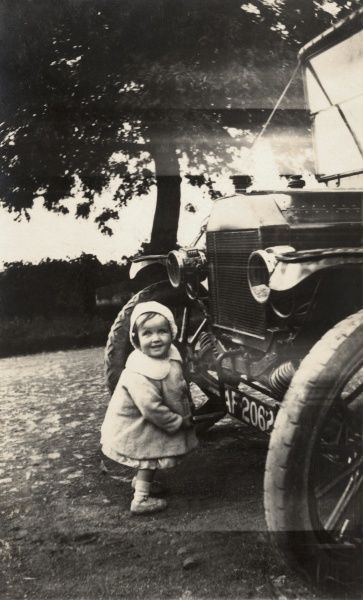 A very little girl beams as she has a photograph taken while turning the crank handle of a very large car