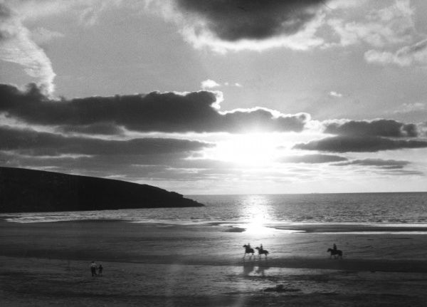 Horse riding on the beach at sunset, Crantock Bay, Cornwall, England. Date: 1960s
