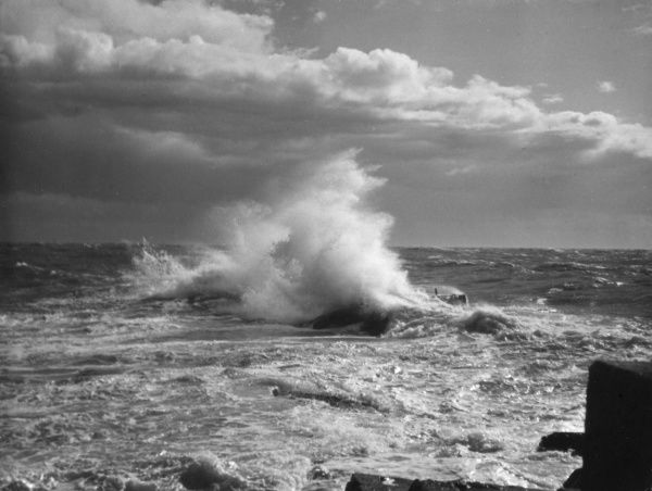 A fine study of waves crashing against the rocks. Date: 1950s