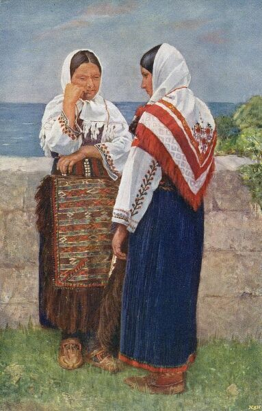 Croatia - Traditional National Costume (3/8) - two women with embroidered white headscarves chatting by a wall facing the coast