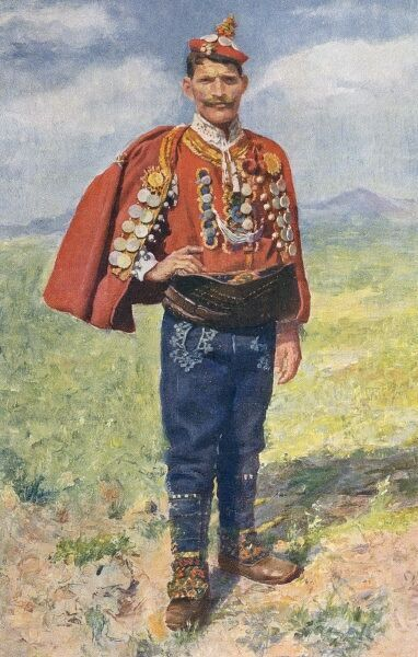 Croatia - Traditional National Costume (5/8) - Full-face view of a young man with hand on hip in decorated jerkin and cape with blue embroidered trousers