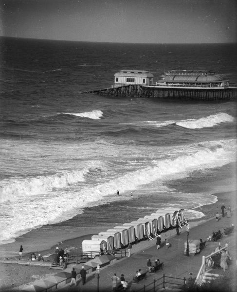 Rough seas on the coast of Norfolk at Cromer, England, with its bathing huts on the beach and pier in the background