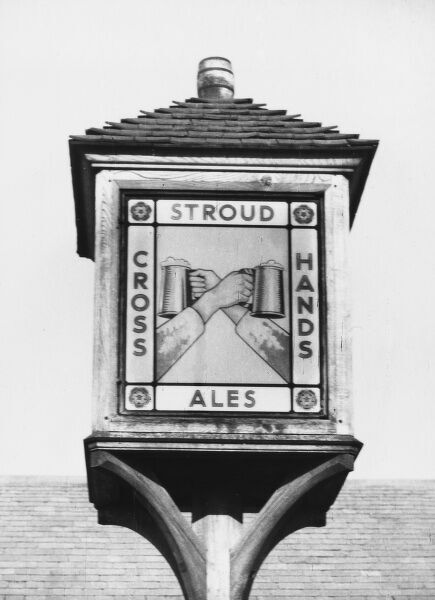 'The Cross Hands' inn sign, near Gloucester, England. This amusing pictorial inn sign shows two hands crossed, holding foaming tankards of ale!