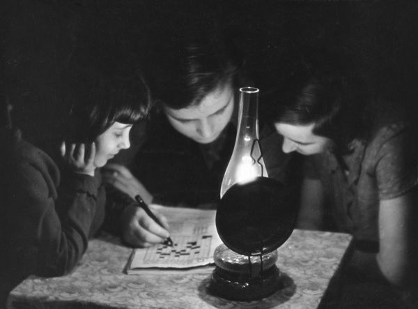 Three children do a crossword by lamp light