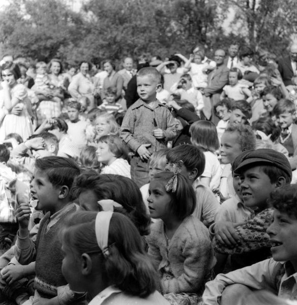 A crowd of children watch a Punch & Judy performance at the Whit Monday Church fete in a park in Thaxted, Essex. Date: 1950s