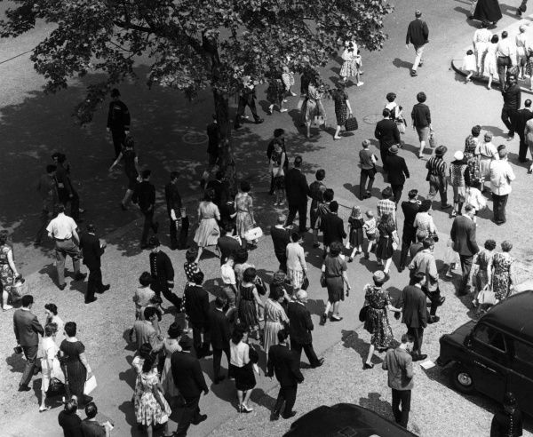 A crowd scene, probably in London, showing the various fashions of the day. Date: mid 1950s