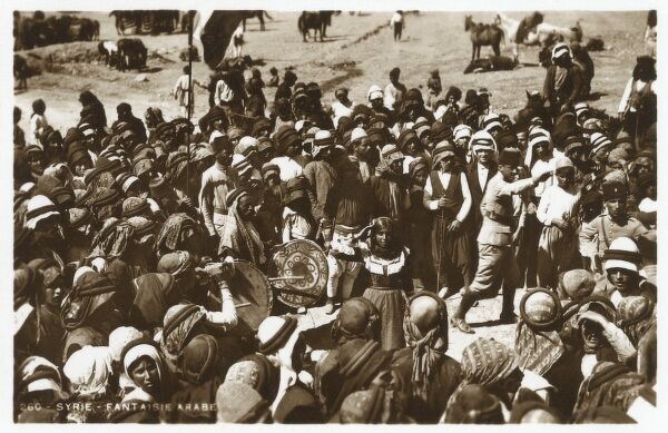 A Crowd of Syrian Arab men and women in traditional costume at a seasonal festival Date: circa 1930s