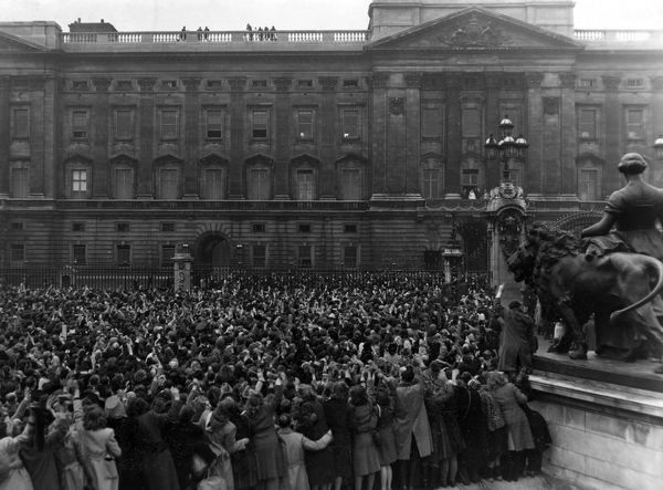 Members of the crowd outside Buckingham Palace crane their necks to view the royal family who have appeared on the balcony to wave after the wedding of Princess Elizabeth (Queen Elizabeth II) to Prince Philip, Duke of Edinburgh at Westminster