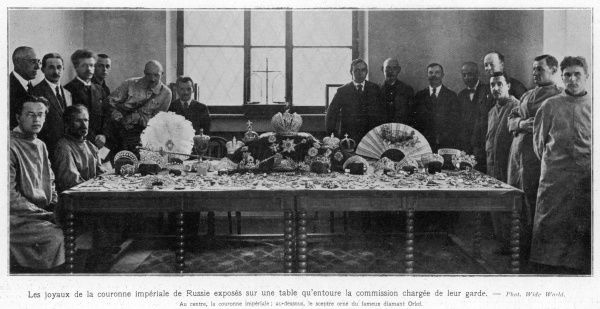 The crown jewels displayed on a table surrounded by the bolsheviks who acquired them, following the demise of Tsar Nicholas II and his family
