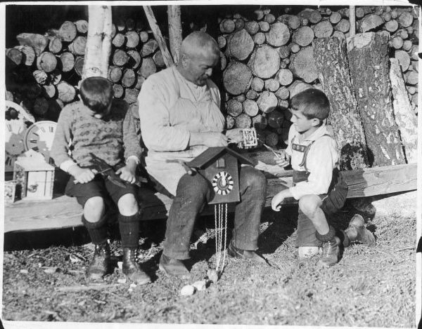 Two little boys help an old clockmaker, perhaps their grandfather, to make a cuckoo clock in the Black Forest, Germany
