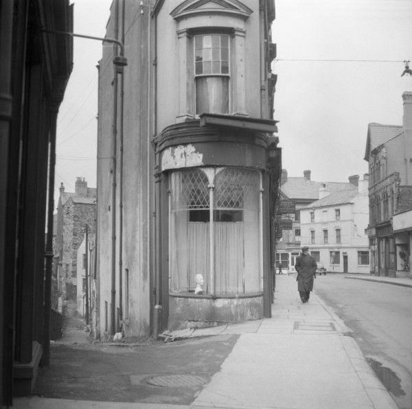 The elegant curved front window of a very narrow house at the end of two diverging streets in Wales. Photograph by Norman Synge Waller Budd